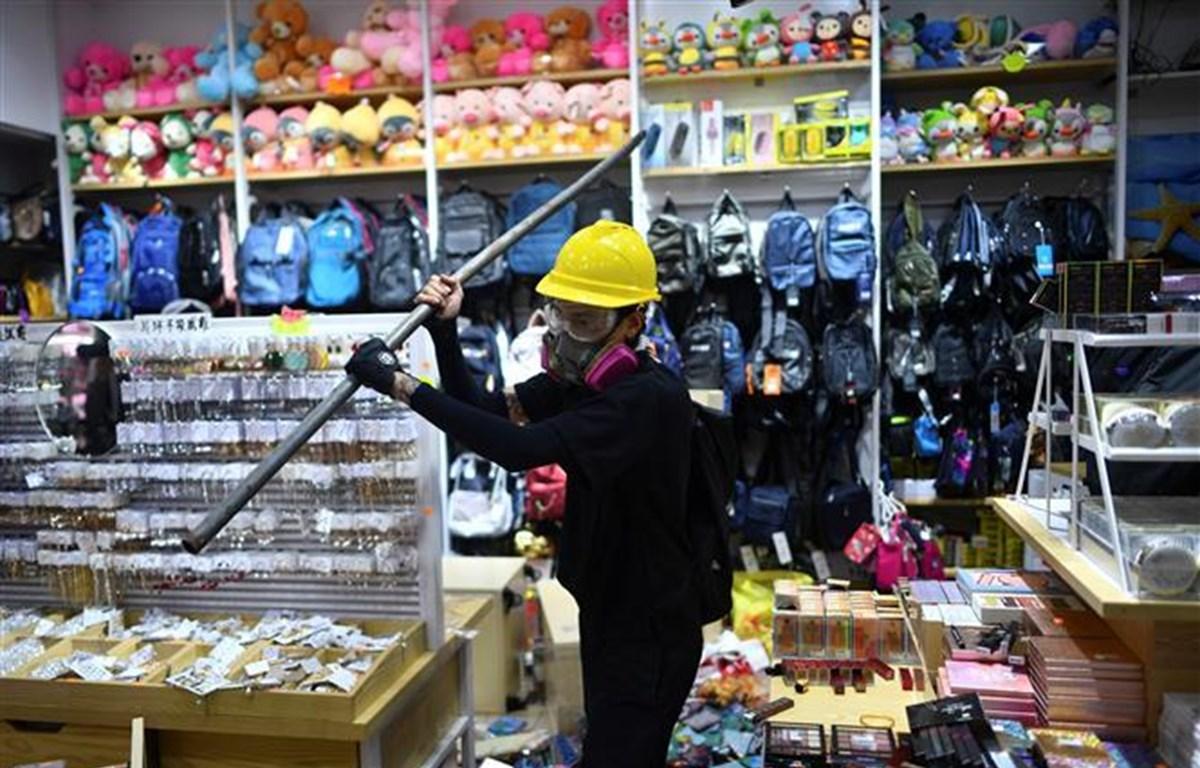 Người biểu tình phá hoại một cửa hàng ở Hong Kong ngày 20/10/2019. (Ảnh: AFP/TTXVN)