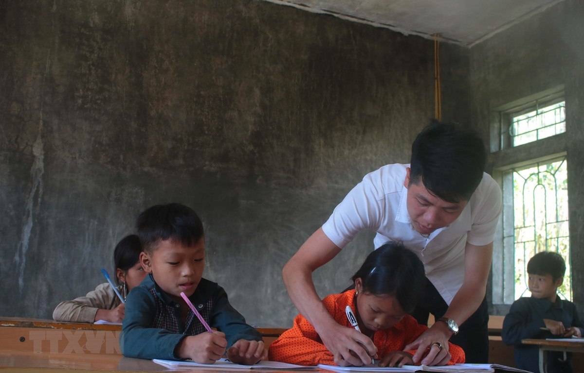 Thầy giáo Hoàng Văn Duy hướng dẫn học sinh viết bài tại điểm trường Hò Lù, xã Khánh Xuân (Bảo Lạc, Cao Bằng). (Ảnh: Chu Hiệu/TTXVN)