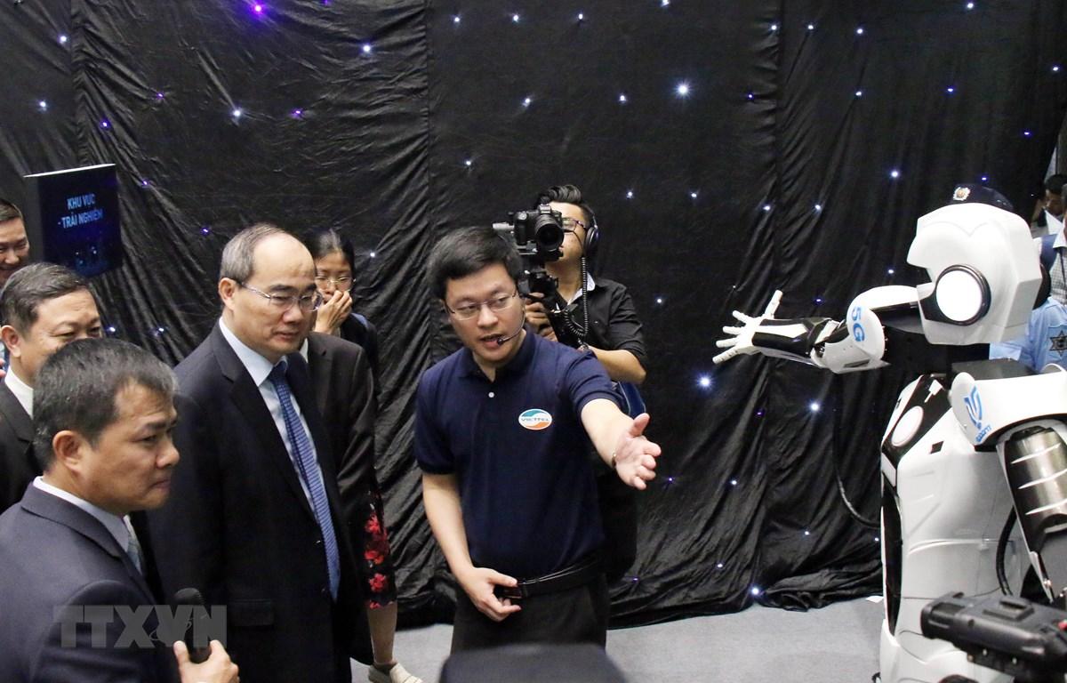 Bí thư Thành ủy Thành phố Hồ Chí Minh Nguyễn Thiện Nhân nghe giới thiệu về robot mô phỏng các động tác được điều khiển từ xa qua sóng 5G. (Ảnh: Tiến Lực/TTXVN)