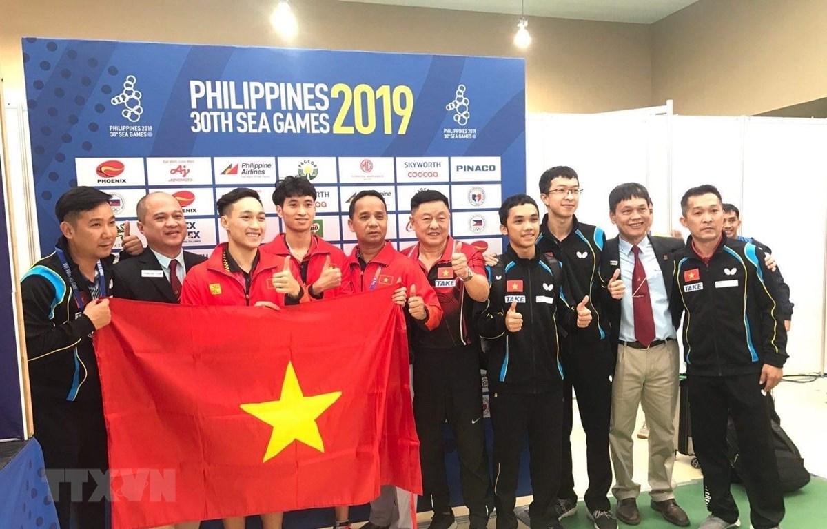 Hai vận động viên Anh Tú (thứ 3, từ trái qua) và Tuấn Anh (thứ 4, từ trái qua) chụp ảnh lưu niệm với Ban huấn luyện và lãnh đạo Đoàn thể thao Việt Nam sau khi giành thắng lợi trong trận chung kết nội dung đôi nam. (Ảnh: Hoàng Linh/TTXVN)