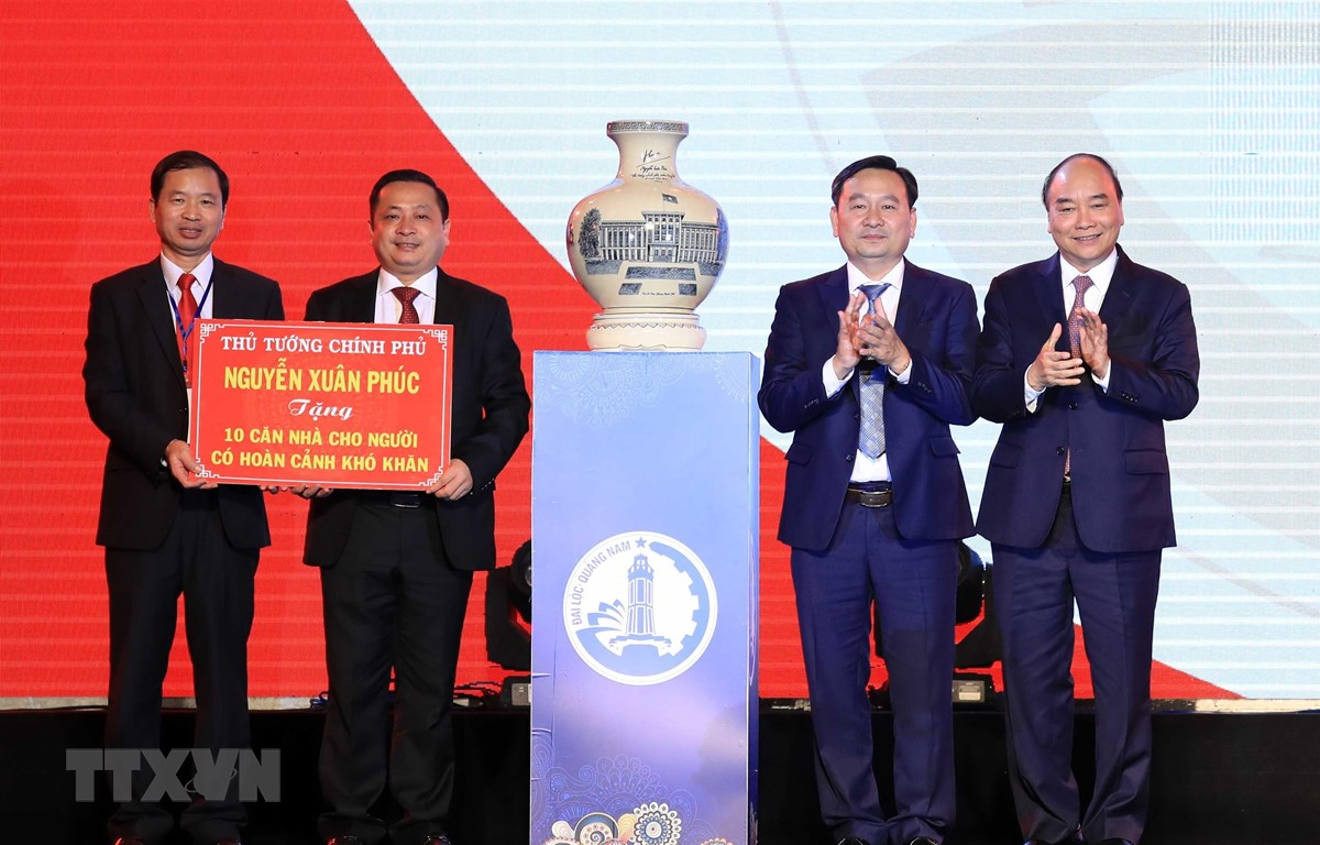 Thủ tướng Nguyễn Xuân Phúc tặng quà lưu niệm và nhà cho người có hoàn cảnh khó khăn huyện Đại Lộc. (Ảnh: Thống Nhất/TTXVN)