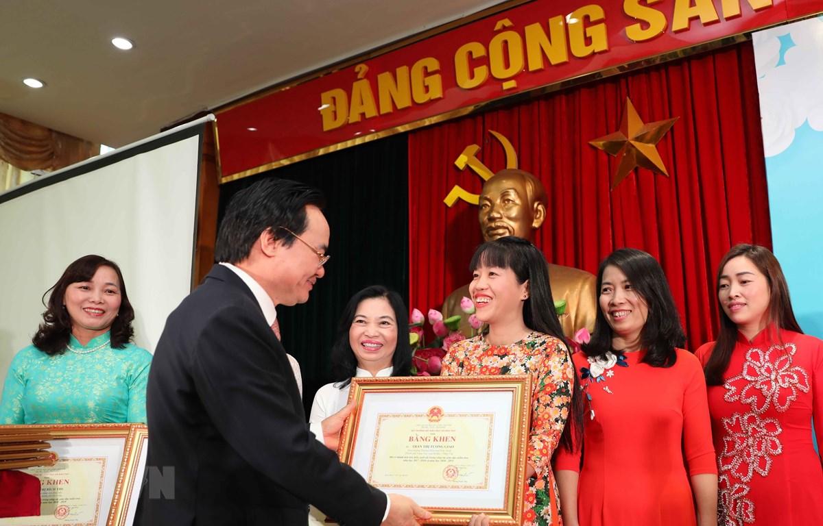 Bộ trưởng Phùng Xuân Nhạ trao bằng khen cho các giáo viên có thành tích xuất sắc trong công tác giáo dục mầm non. (Ảnh: Thanh Tùng/TTXVN)