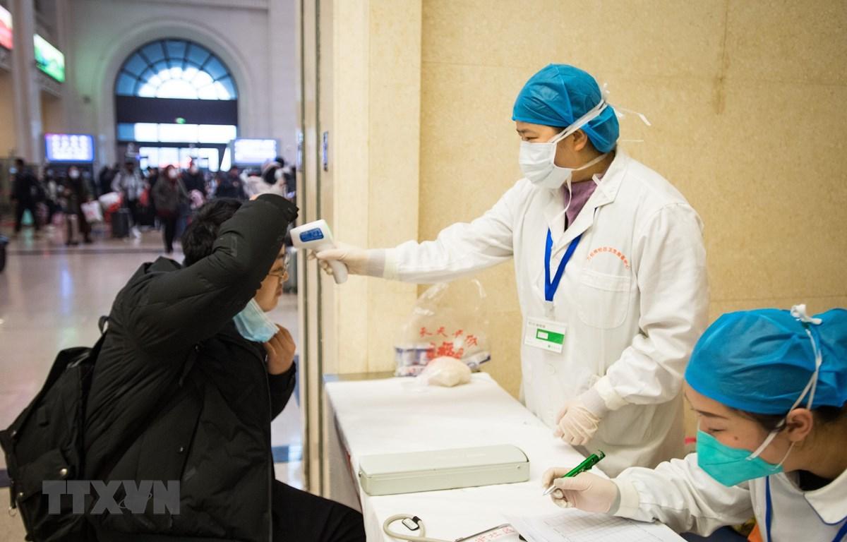 Nhân viên y tế kiểm tra thân nhiệt của hành khách tại một nhà ga ở Vũ Hán, thủ phủ tỉnh Hồ Bắc, Trung Quốc ngày 22/1/2020. (Ảnh: THX/TTXVN)