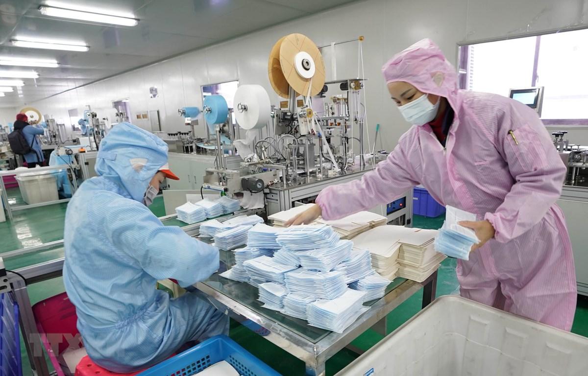 Công nhân nỗ lực may khẩu trang y tế tại một nhà máy ở Vũ Hán, Trung Quốc. (Ảnh: THX/TTXVN)