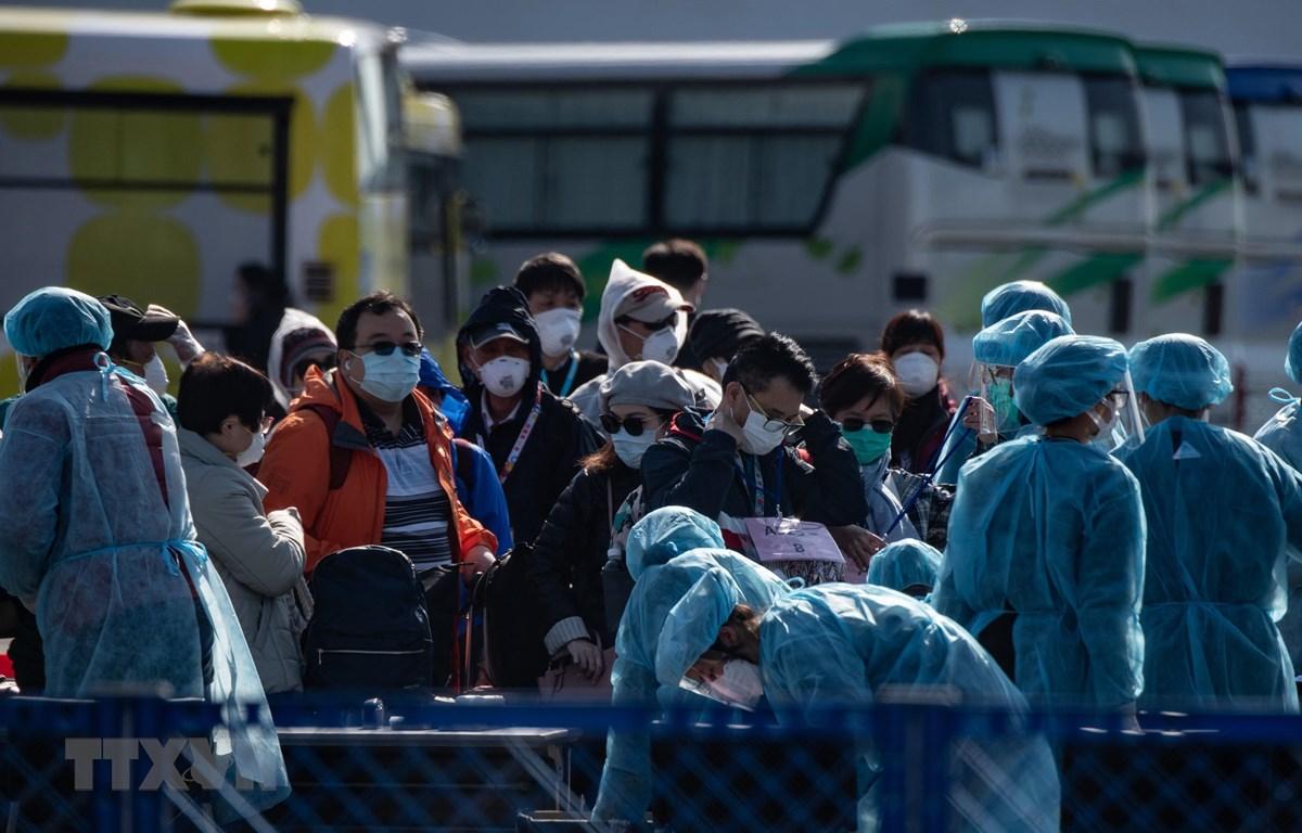 Hành khách được kiểm tra thân nhiệt trước khi rời khỏi du thuyền Diamond Princess tại cảng ở Yokohama, Nhật Bản ngày 21/2/2020. (Ảnh: AFP/TTXVN)