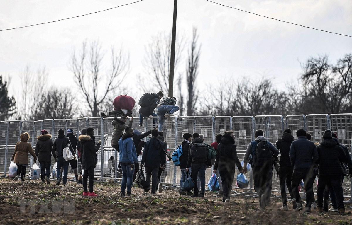 Người di cư cố vượt qua hàng rào ở biên giới giữa Thổ Nhĩ Kỳ và Hy Lạp trong hành trình tới châu Âu ngày 4/3/2020. (Ảnh: AFP/TTXVN)