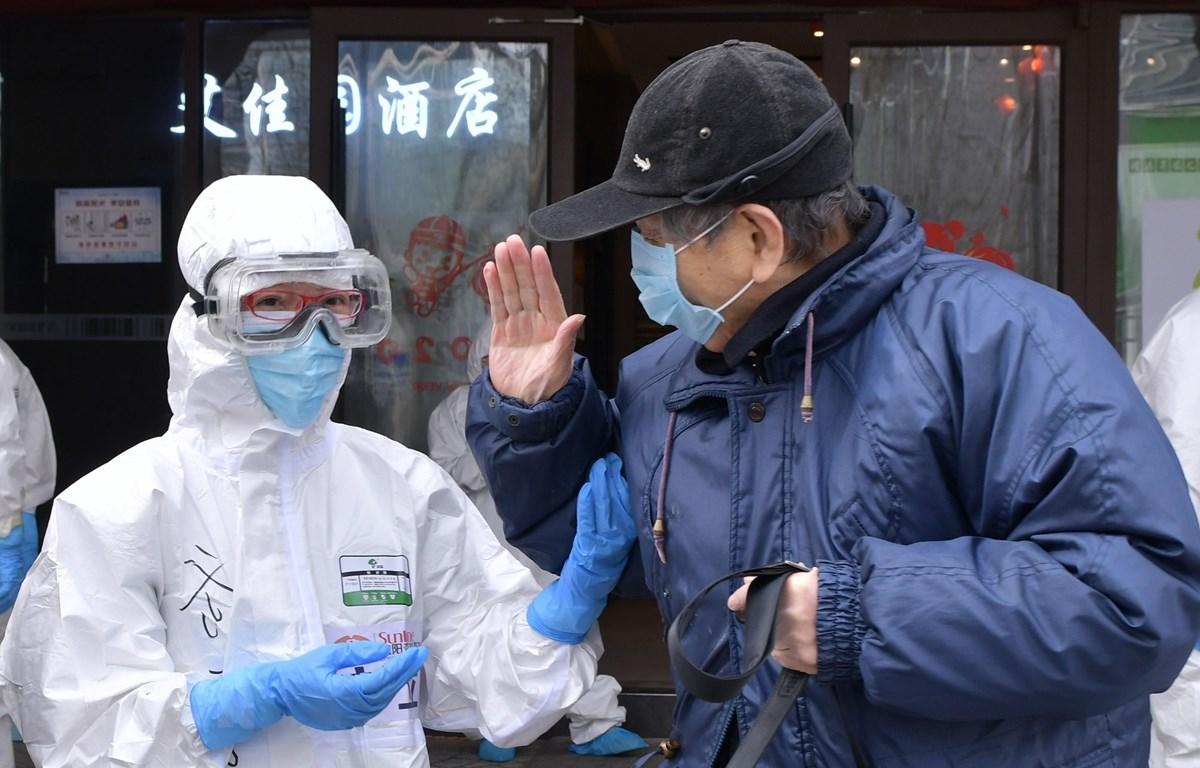 Bệnh nhân nhiễm COVID-19 tạm biệt bác sĩ sau khi được chữa khỏi tại bệnh viện ở Vũ Hán, tỉnh Hồ Bắc, Trung Quốc, ngày 10/3/2020. (Ảnh: THX/TTXVN)