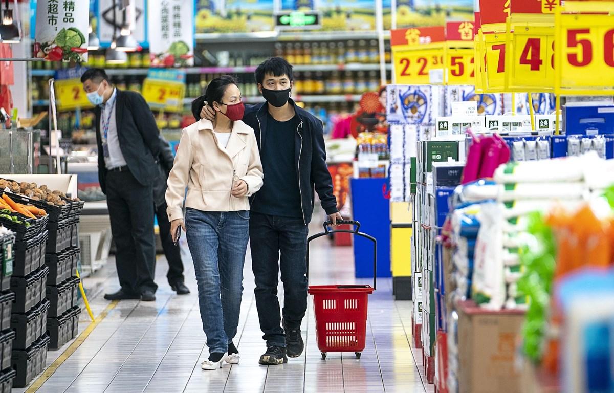 Người dân đeo khẩu trang để phòng tránh lây nhiễm COVID-19 tại siêu thị ở Vũ Hán, tỉnh Hồ Bắc, Trung Quốc, ngày 24/3/2020. (Ảnh: THX/TTXVN)
