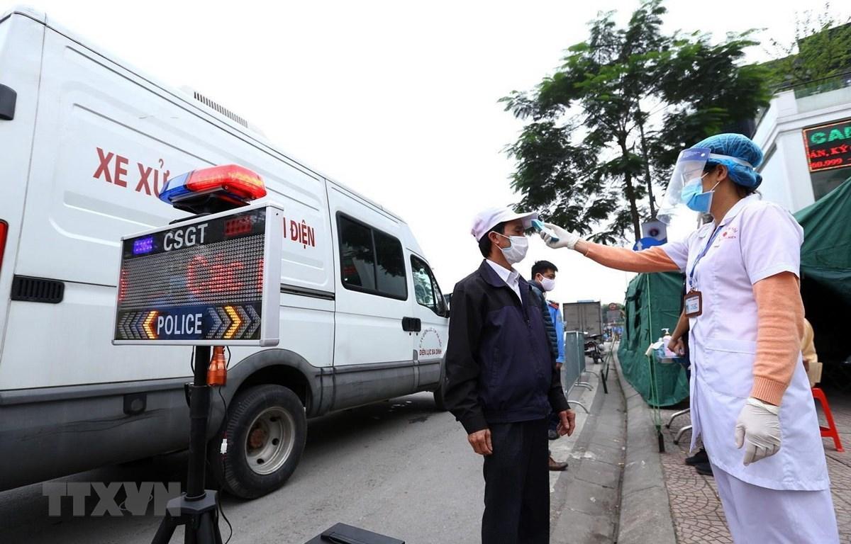 Nhân viên y tế kiểm tra thân nhiệt cho tài xế tại chốt kiểm soát phía Bắc cầu Chương Dương hướng vào nội thành Hà Nội. (Ảnh: Minh Quyết/TTXVN)
