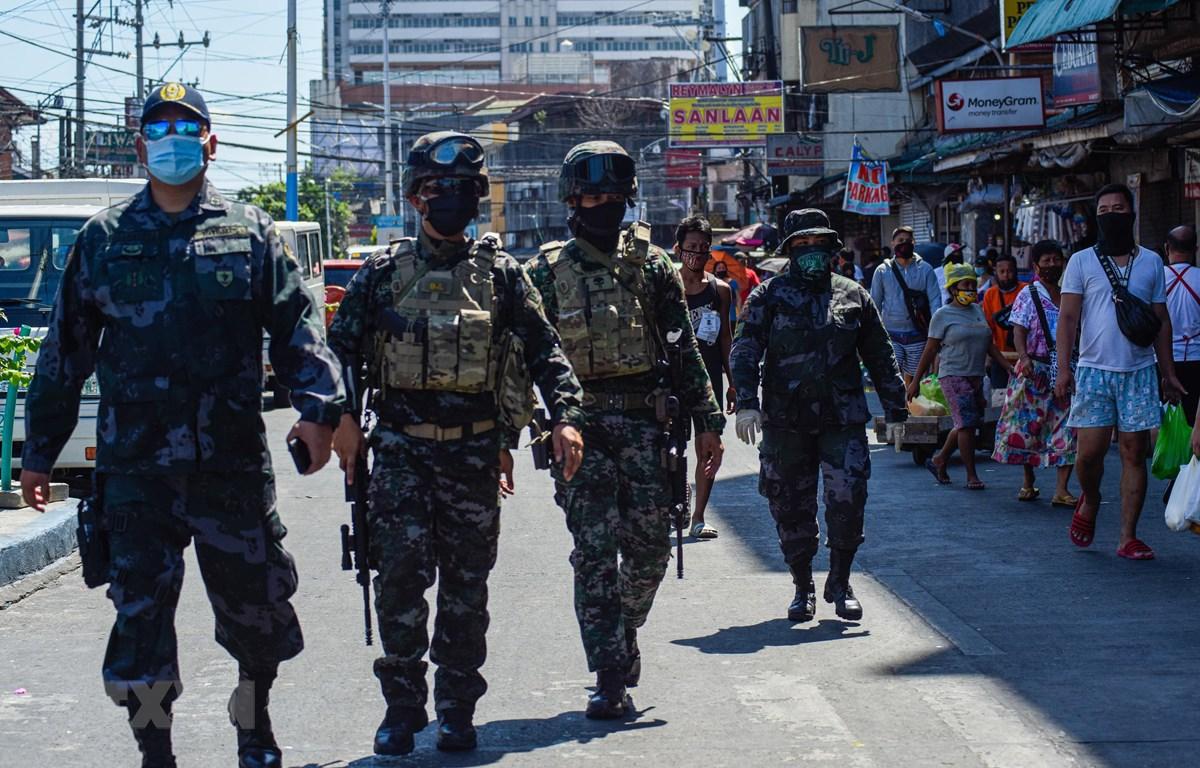 Cảnh sát tuần tra nhắc nhở người dân về các biện pháp phòng tránh dịch COVID-19 tại một chợ ở Manila, Philippines. (Ảnh: AFP/TTXVN)