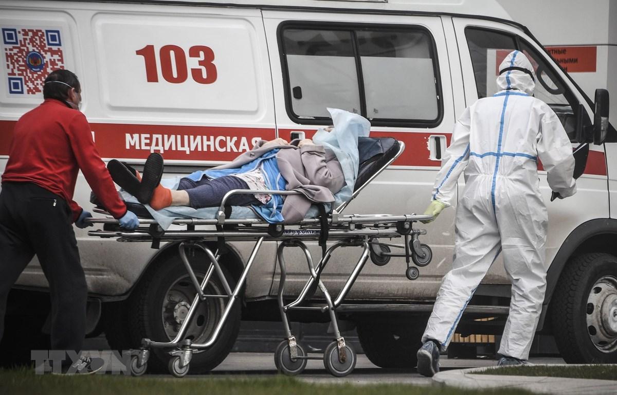 Nhân viên y tế chuyển bệnh nhân nhiễm COVID-19 tới bệnh viện ở Moskva, Nga. (Ảnh: AFP/TTXVN)
