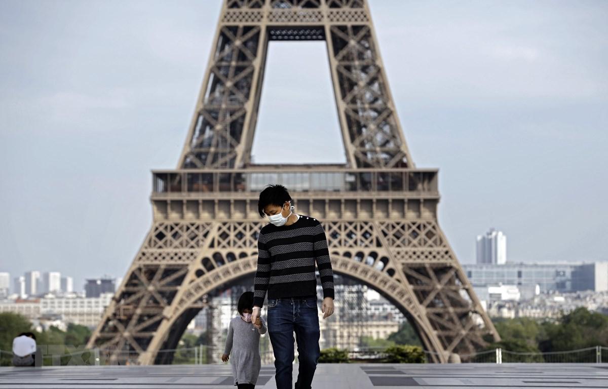 Người dân đeo khẩu trang nhằm ngăn chặn sự lây lan của dịch COVID-19 tại Paris, Pháp. (Ảnh: AFP/TTXVN)