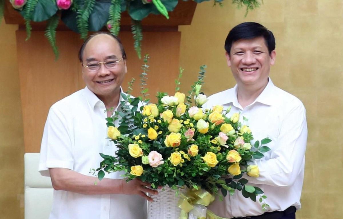 Thủ tướng Nguyễn Xuân Phúc chúc mừng quyền Bộ trưởng Bộ Y tế Nguyễn Thanh Long tại Trụ sở Chính phủ hôm 10/7. (Ảnh: Thống Nhất/TTXVN)