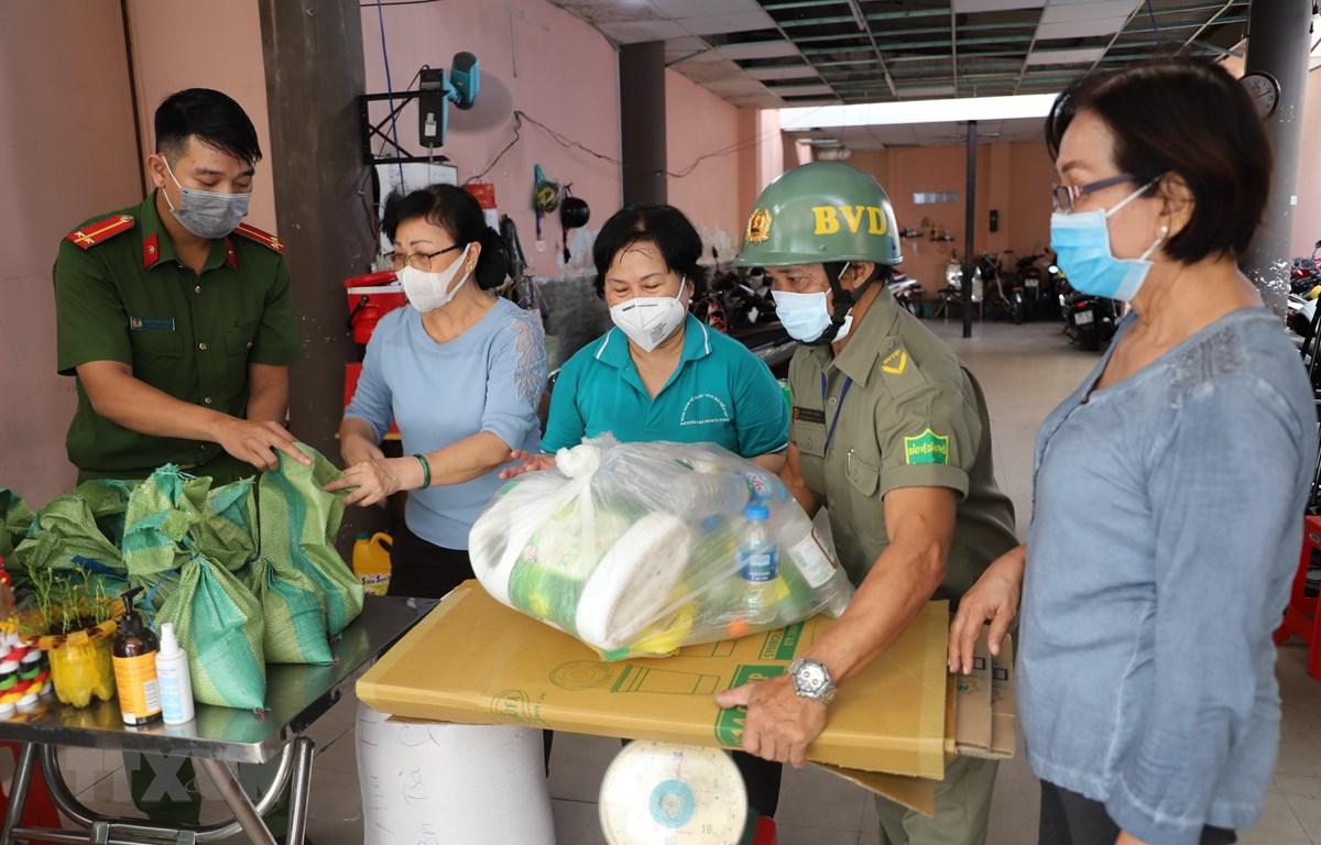Các tình nguyện viên tiến hành cân gạo cho người dân mang rác nhựa đến đổi. (Ảnh: Hồng Giang/TTXVN)