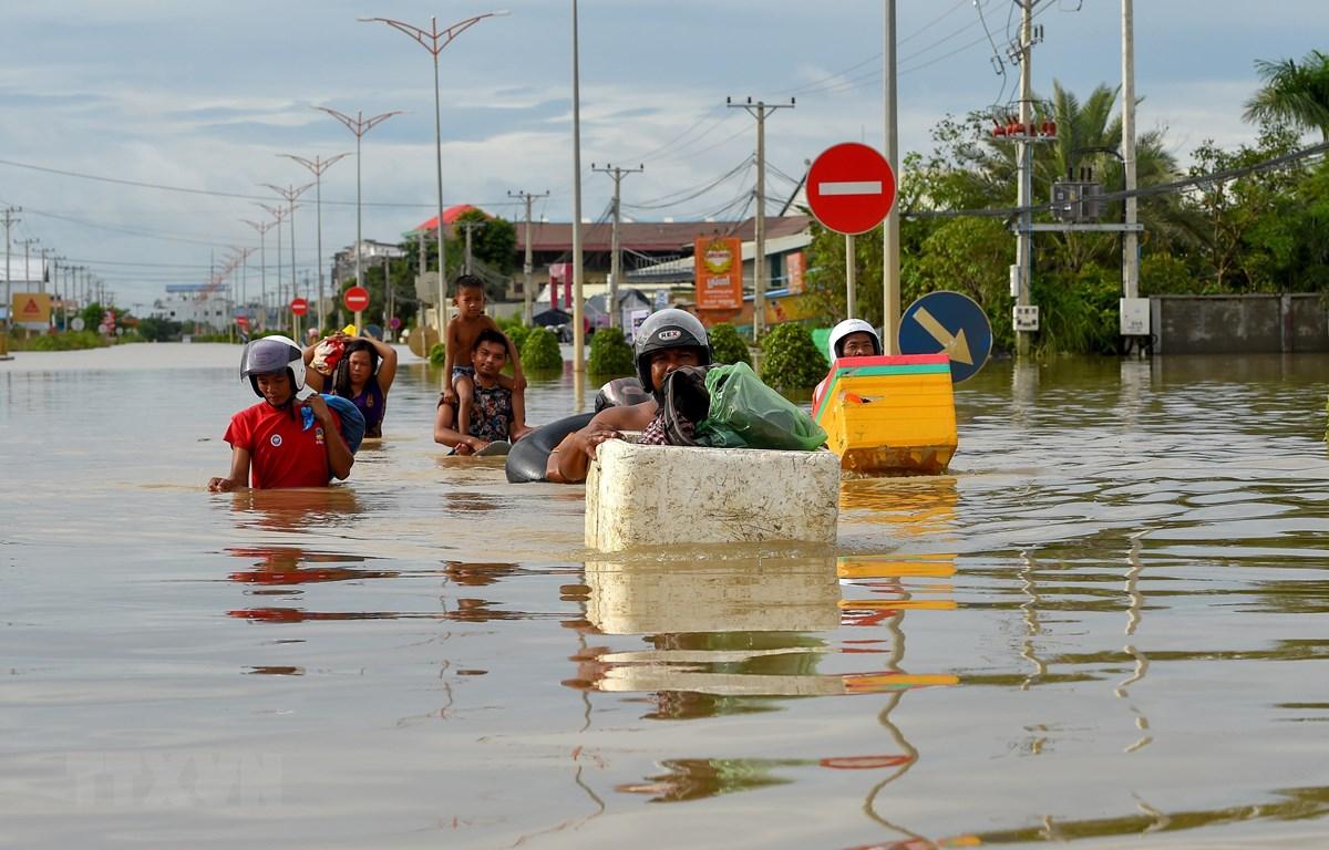 Người dân sơ tán khỏi các khu vực ngập lụt ở Phnom Penh, Campuchia, ngày 17/10/2020. (Ảnh: AFP/TTXVN)