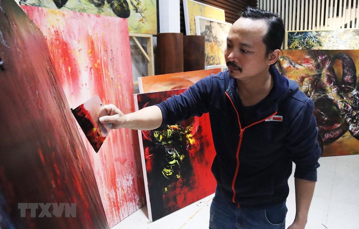 Họa sỹ Ngô Thanh Hùng sáng tác tranh tại nhà. (Ảnh: Văn Dũng/TTXVN)