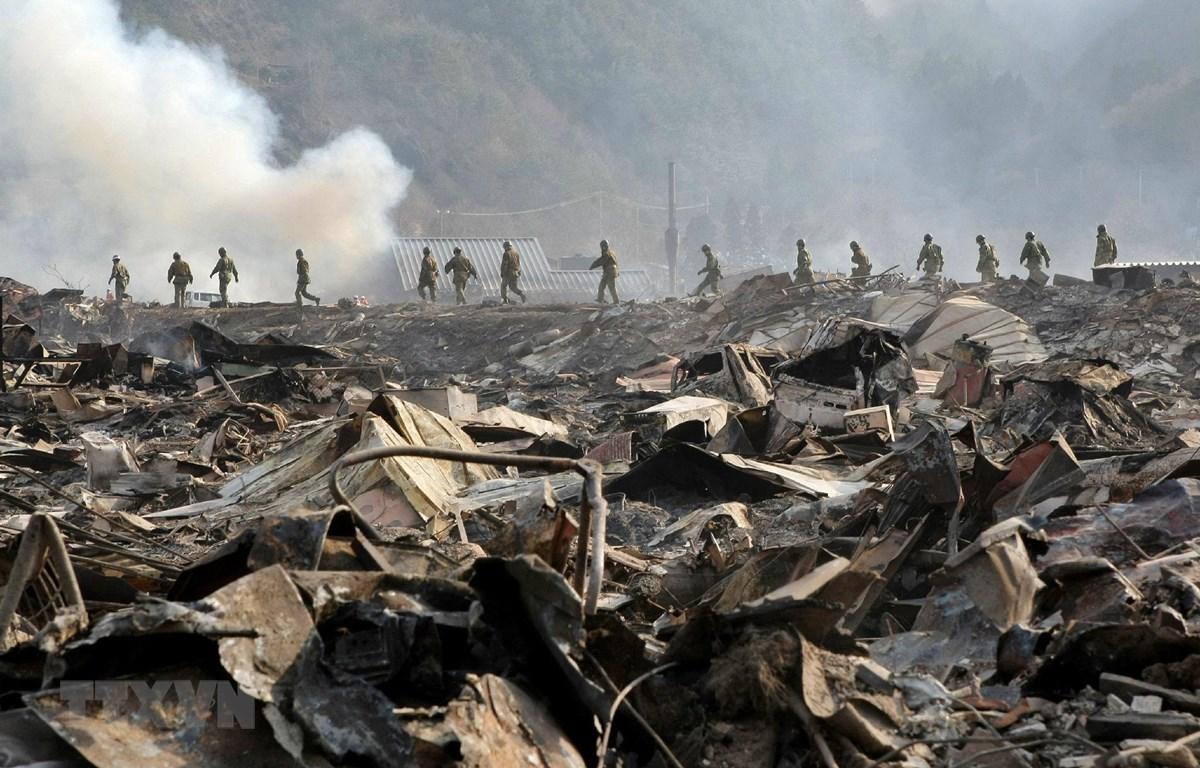 Lực lượng Phòng vệ Nhật Bản tìm kiếm nạn nhân tại khu vực bị tàn phá sau thảm họa động đất sóng thần ở tỉnh Iwate, Nhật Bản ngày 13/3/2011. (Ảnh: AFP/TTXVN)