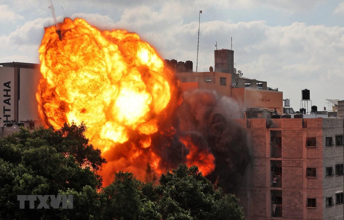 Quả cầu lửa bốc lên khi toà nhà Al-Walid ở thành phố Gaza trúng rocket trong cuộc oanh tạc của máy bay Israel ngày 13/5/2021. (Ảnh: AFP/TTXVN)