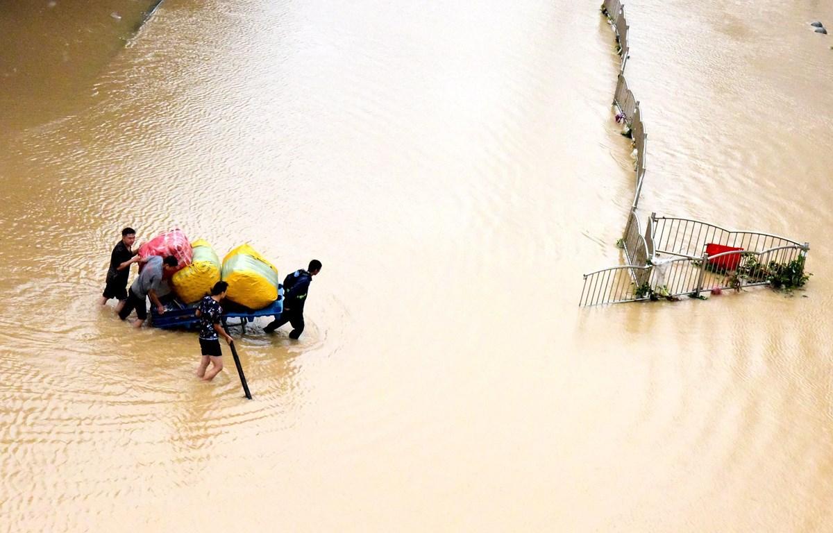 Người dân sơ tán khỏi vùng ngập lụt tại Trịnh Châu, tỉnh Hà Nam, Trung Quốc. (Ảnh: THX/TTXVN)