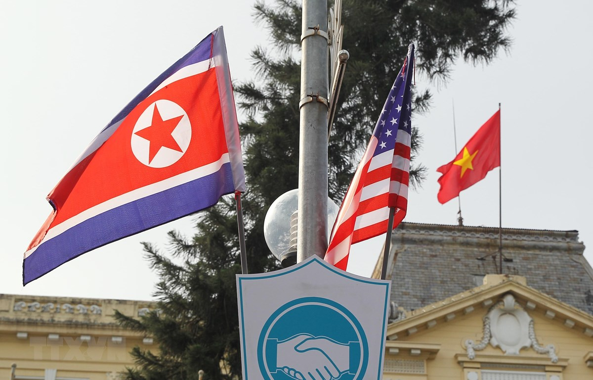 Cờ Mỹ và cờ Triều Tiên, bên dưới là biểu tượng hai bàn tay bắt chặt vào nhau thể hiện tinh thần của cuộc gặp lớn, được treo bên ngoài Nhà khách Chính phủ trên phố Ngô Quyền, Quận Hoàn Kiếm. (Ảnh: Lâm Khánh/TTXVN)
