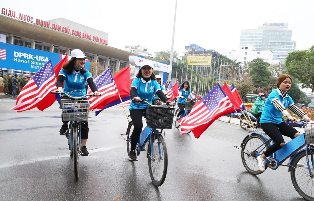 Thiếu nữ Việt Nam diễn hành Đạp xe vì Hòa bình với quốc kỳ Việt Nam và hai nước Mỹ, Triều Tiên trên đường Trần Hưng Đạo, Hoàn Kiếm. (Ảnh: Lâm Khánh/TTXVN)