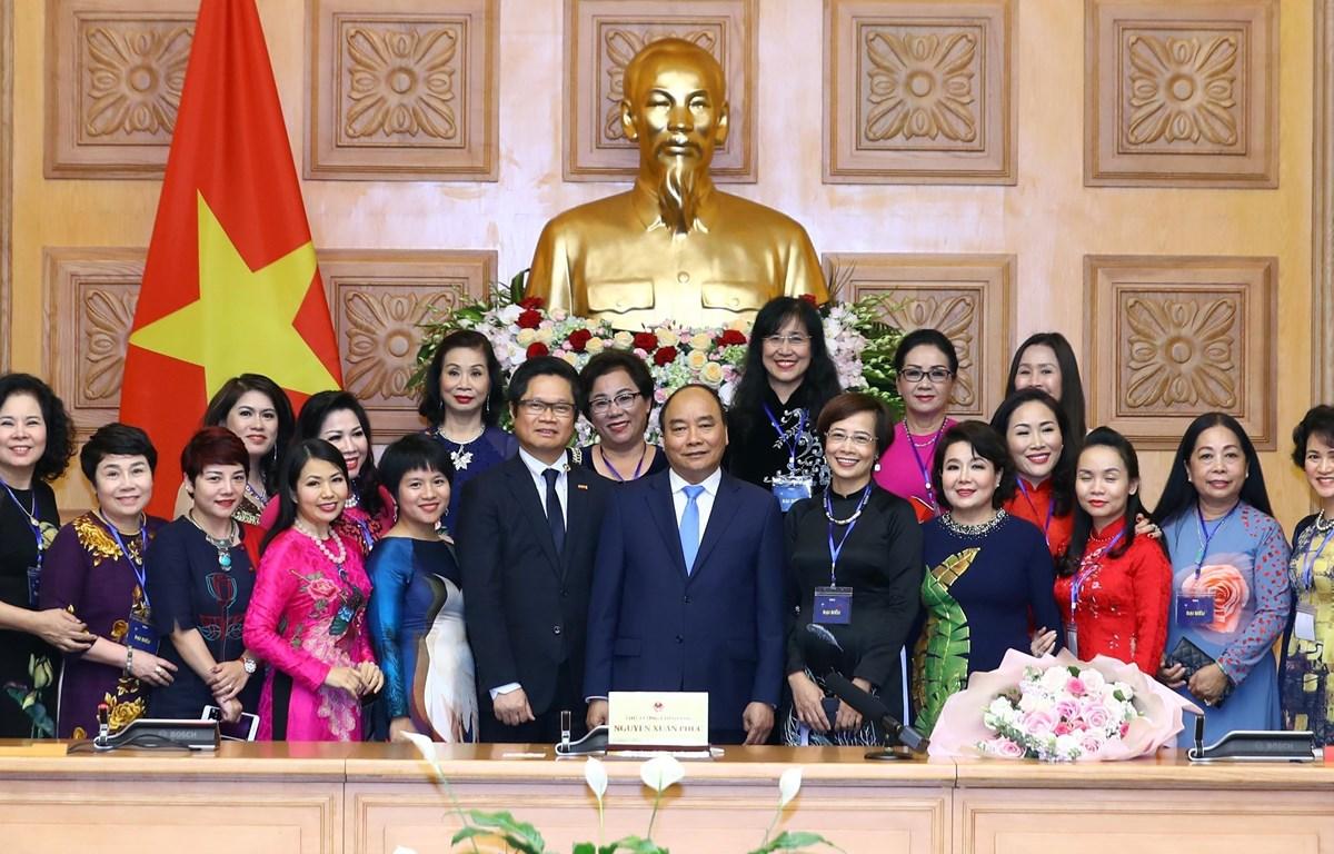 Thủ tướng Nguyễn Xuân Phúc chụp ảnh với các nữ doanh nhân tiêu biểu tại buổi gặp mặt. (Ảnh: Thống Nhất/TTXVN)
