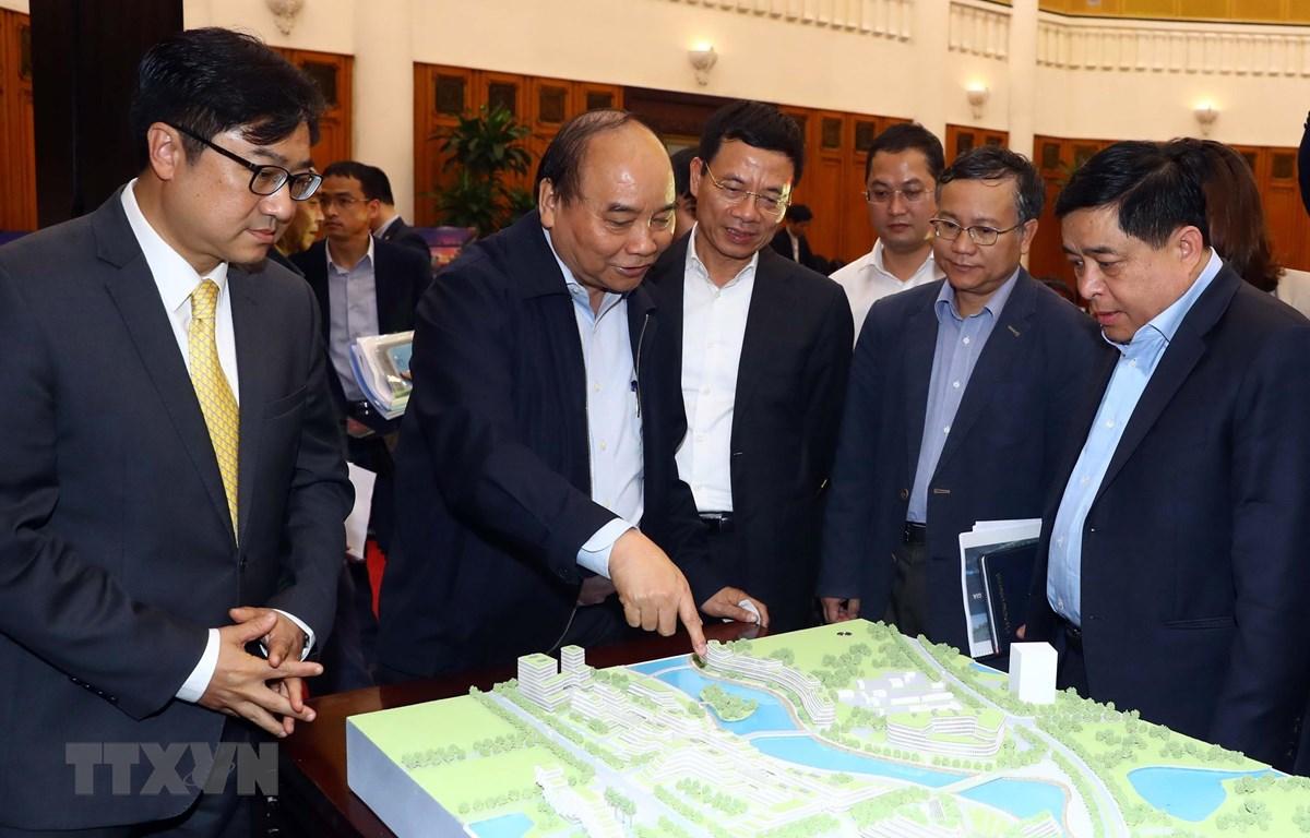 Thủ tướng Nguyễn Xuân Phúc và các đại biểu xem mô hình Trung tâm đổi mới sáng tạo quốc gia. Ảnh: Thống Nhất/TTXVN)