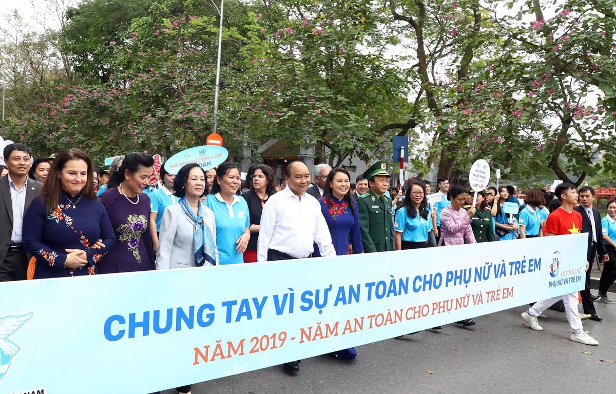 Thủ tướng Nguyễn Xuân Phúc và các đại biểu cùng tham gia đi bộ trên đường Đinh Tiên Hoàng, hưởng ứng Năm an toàn cho phụ nữ và trẻ em. (Ảnh: Thống Nhất/TTXVN)