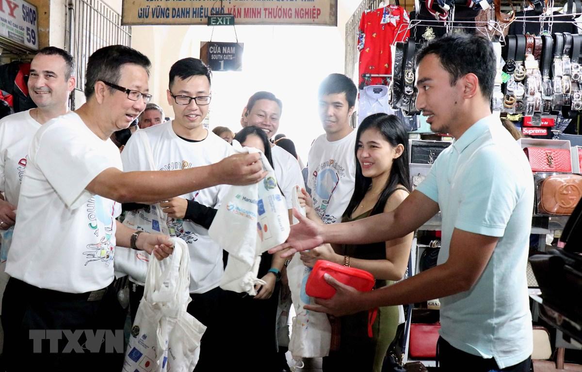 Ông Phạm Đức Hải, Phó Chủ tịch Hội đồng Nhân dân Thành phố Hồ Chí Minh phát tặng túi vải tái sử dụng cho người đi chợ Bến Thành. (Ảnh: Xuân Khu/TTXVN)