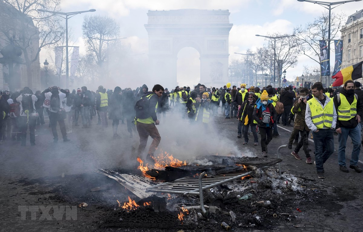 Người biểu tình Áo vàng đốt các rào chắn trên đại lộ Champs-Elysees ở Paris, Pháp, ngày 16/3. (Nguồn: THX/TTXVN)
