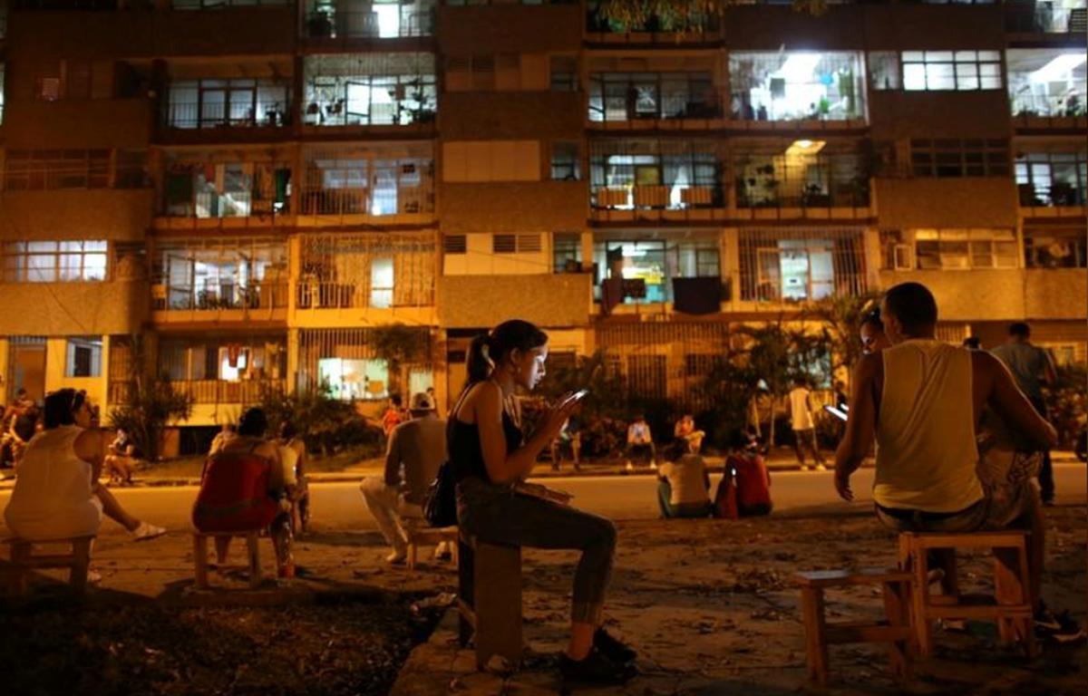 Người dân Cuba sử dụng điện thoại di động để kết nối Internet tại một điểm phát mạng không dây ở trung tâm La Habana, Cuba. (Nguồn: REUTERS)