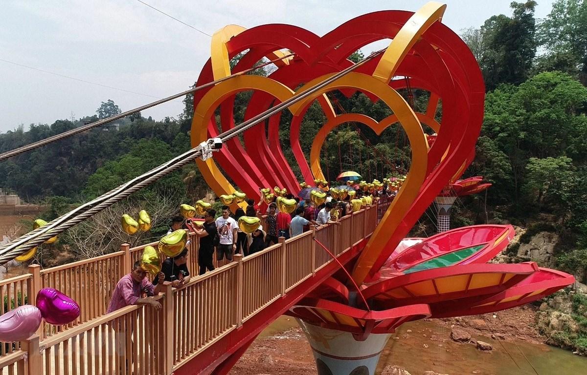Du khách tham quan và trải nghiệm cầu kính tình yêu tại Khu du lịch sinh thái thác Dải Yếm, huyện Mộc Châu, tỉnh Sơn La. (Nguồn: TTXVN phát)