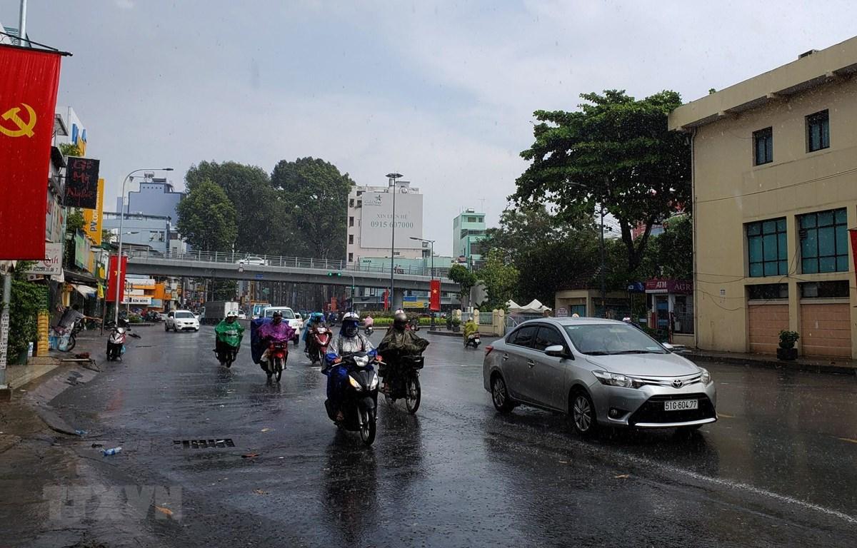Người dân lưu thông trong mưa trên đường Thành Thái, Quận 10. (Ảnh: Xuân Dự/TTXVN)