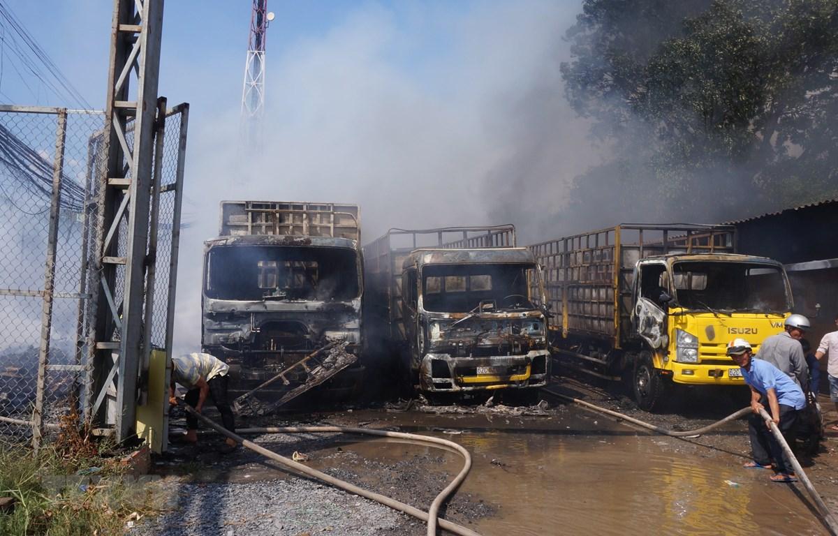 Vụ cháy làm 3 xe tải và nhiều tài sản khác bị thiêu rụi. (Ảnh: Bùi Giang/TTXVN)