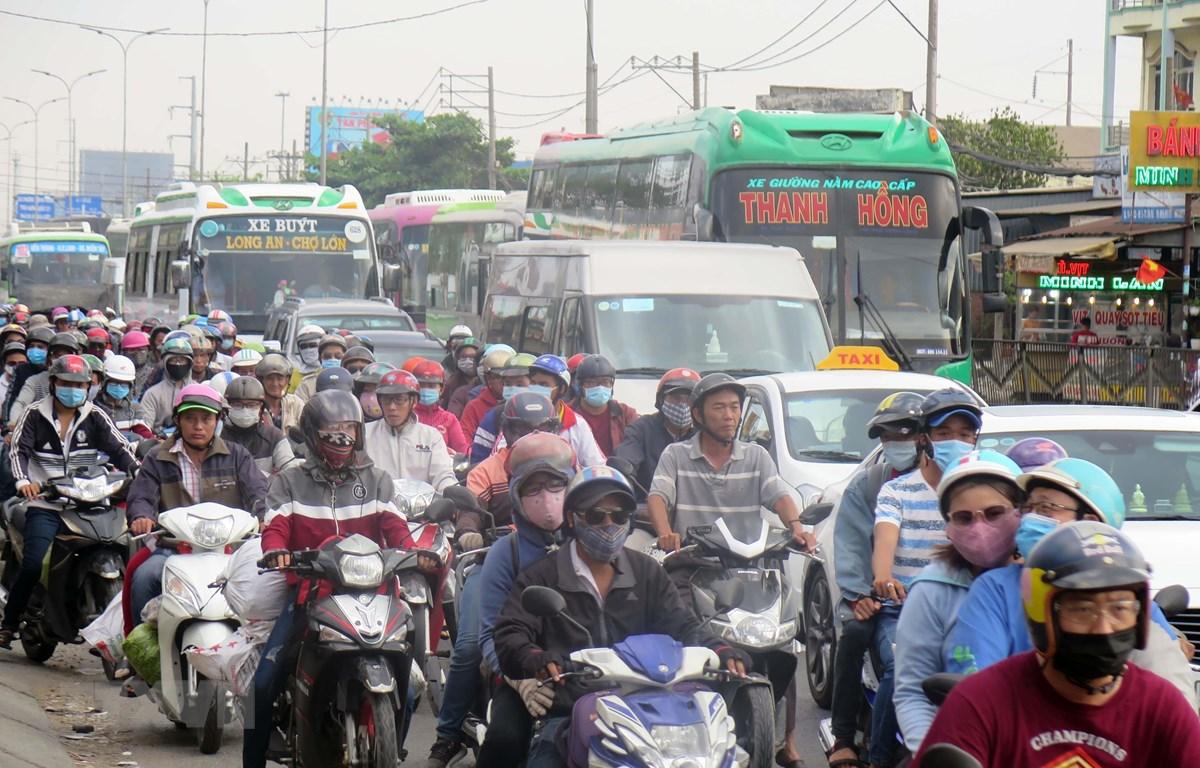 Người dân trở lại Thành phố Hồ Chí Minh trên tuyến quốc lộ 1A (huyện Bình Chánh). (Ảnh: Hoàng Hải/TTXVN)