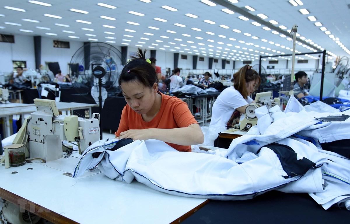 Công nhân sản xuất hàng may mặc tại Công ty trách nhiệm hữu hạn Kydo Việt Nam. (Ảnh: Phạm Kiên/TTXVN)