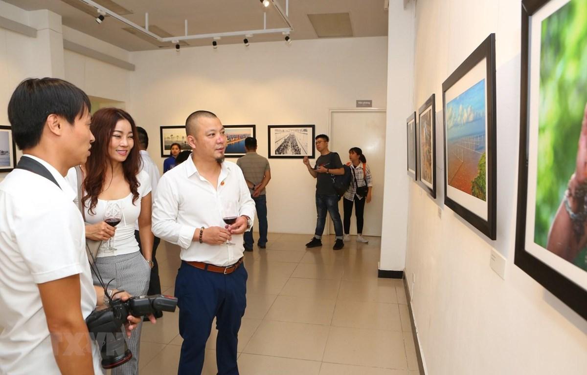 """Các đại biểu và du khách tham quan triển lãm ảnh báo chí """"Dấu ấn."""" (Ảnh: Thành Đạt/TTXVN)"""
