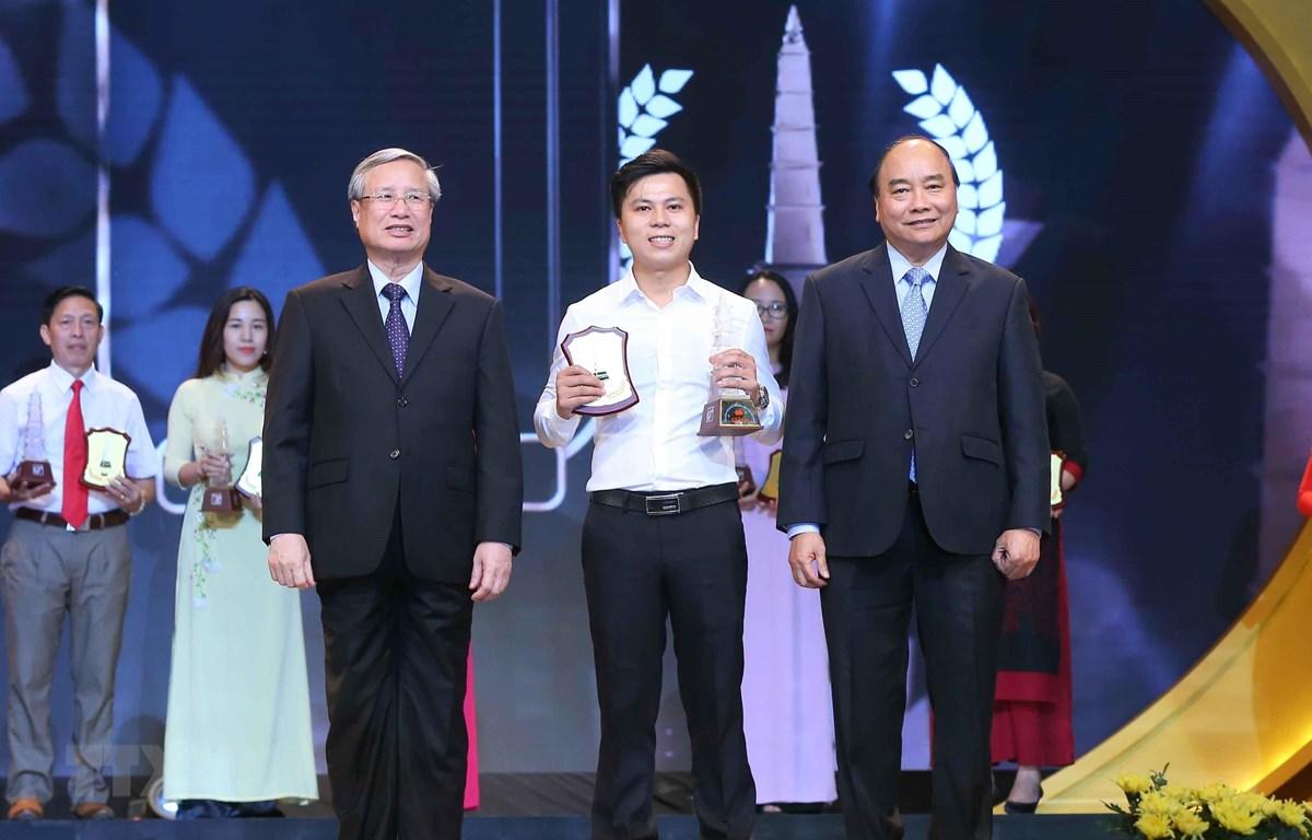 Thủ tướng Nguyễn Xuân Phúc và đồng chí Trần Quốc Vương, Ủy viên Bộ Chính trị, Thường trực Ban Bí thư trao giải A cho tác giả Hùng Võ báo điện tử Vietnamplus, TTXVN. (Ảnh: Doãn Tấn/TTXVN)