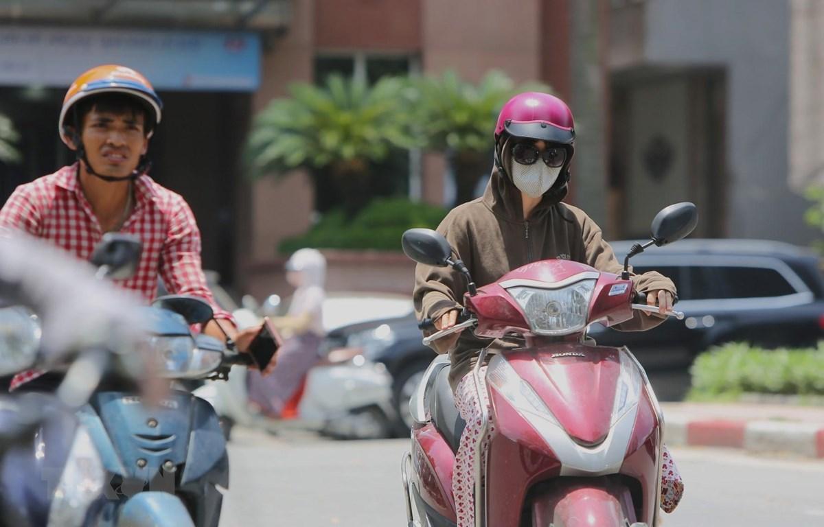 Người dân ra đường với trang phục kín mít để tránh cái nắng gay gắt. (Ảnh: Thành Đạt/TTXVN)