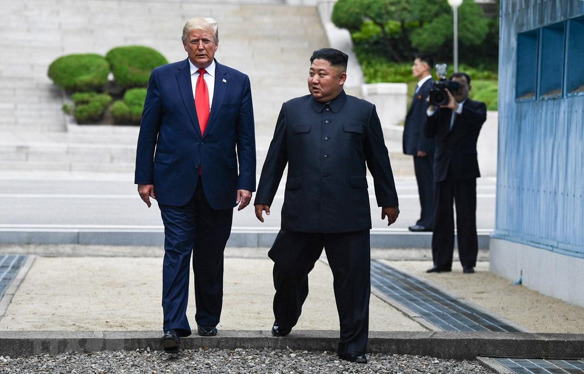 Tổng thống Mỹ Donald Trump (trái) và nhà lãnh đạo Triều Tiên Kim Jong-un bước chân qua đường ranh giới phân chia hai miền Triều Tiên tại DMZ, sang phần lãnh thổ của Triều Tiên chiều 30/6/2019. (Nguồn: AFP/TTXVN)