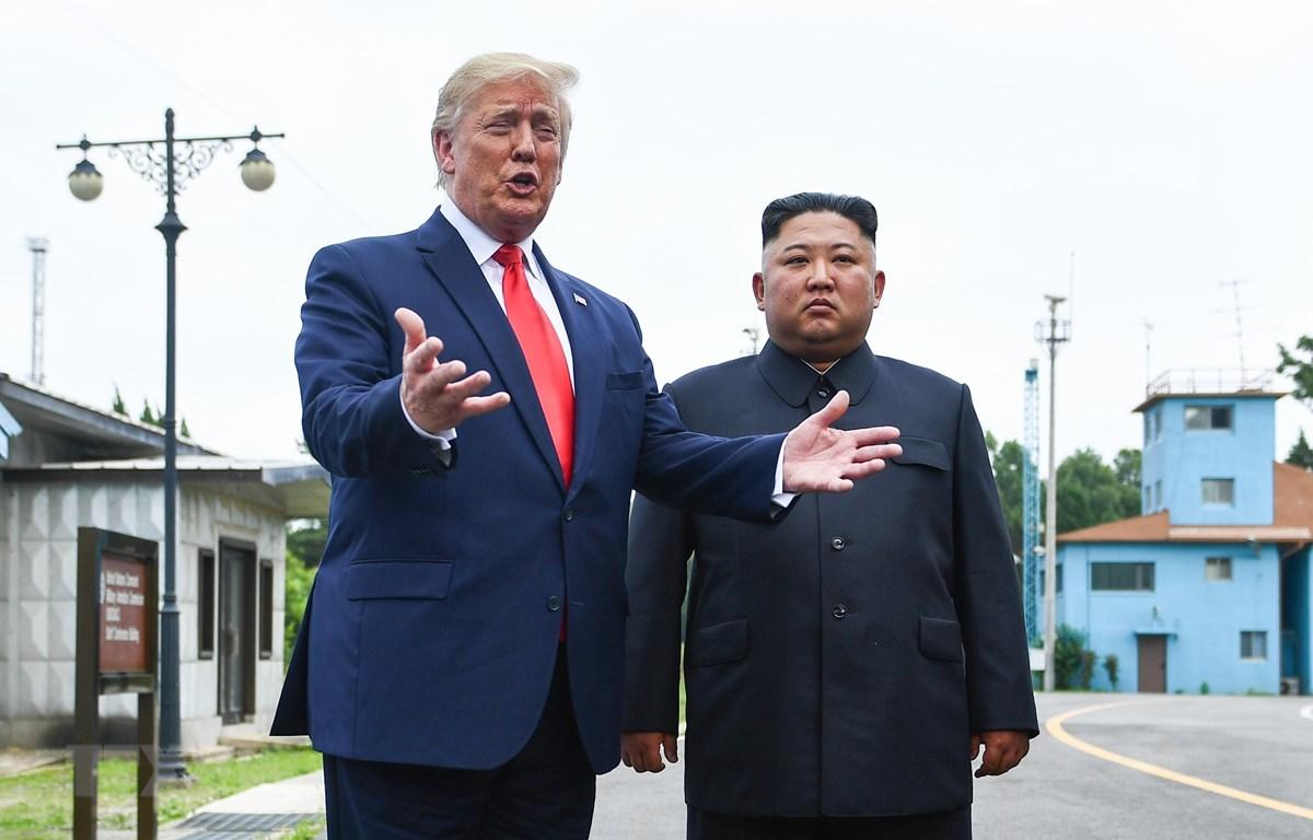Tổng thống Mỹ Donald Trump (trái) và nhà lãnh đạo Triều Tiên Kim Jong-un trong cuộc gặp ở làng đình chiến Panmunjom tại Khu phi quân sự (DMZ) chiều 30/6/2019. (Nguồn: AFP/TTXVN)