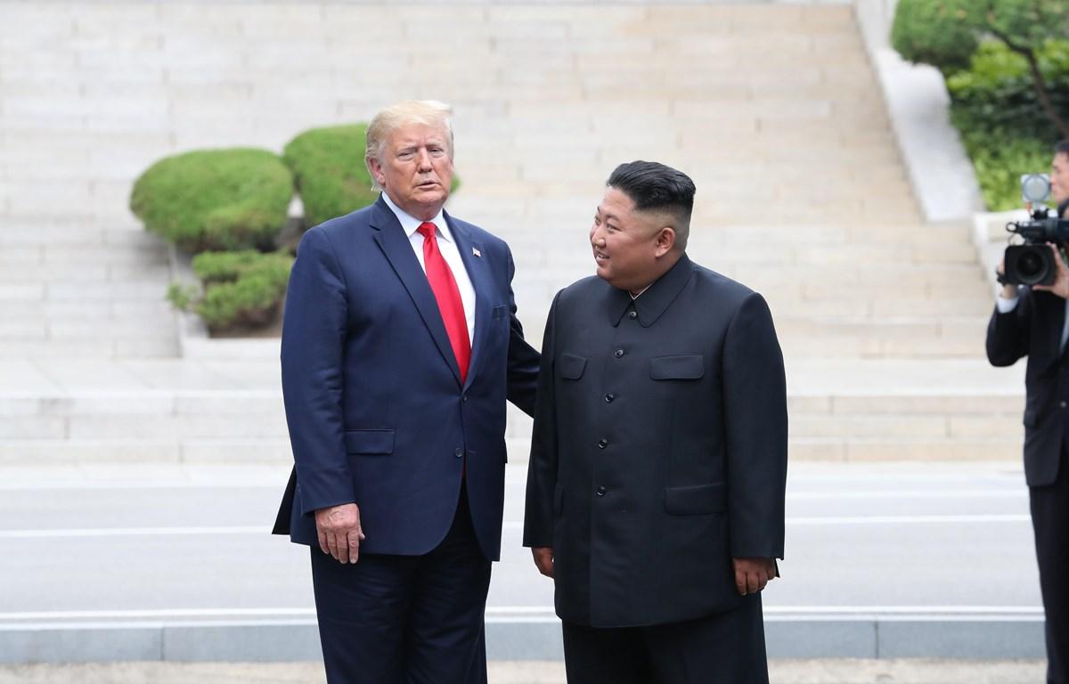 Tổng thống Mỹ Donald Trump (trái) và nhà lãnh đạo Triều Tiên Kim Jong-un trong cuộc gặp ở làng đình chiến Panmunjom tại Khu phi quân sự (DMZ) chiều 30/6/2019. (Nguồn: Yonhap/TTXVN)