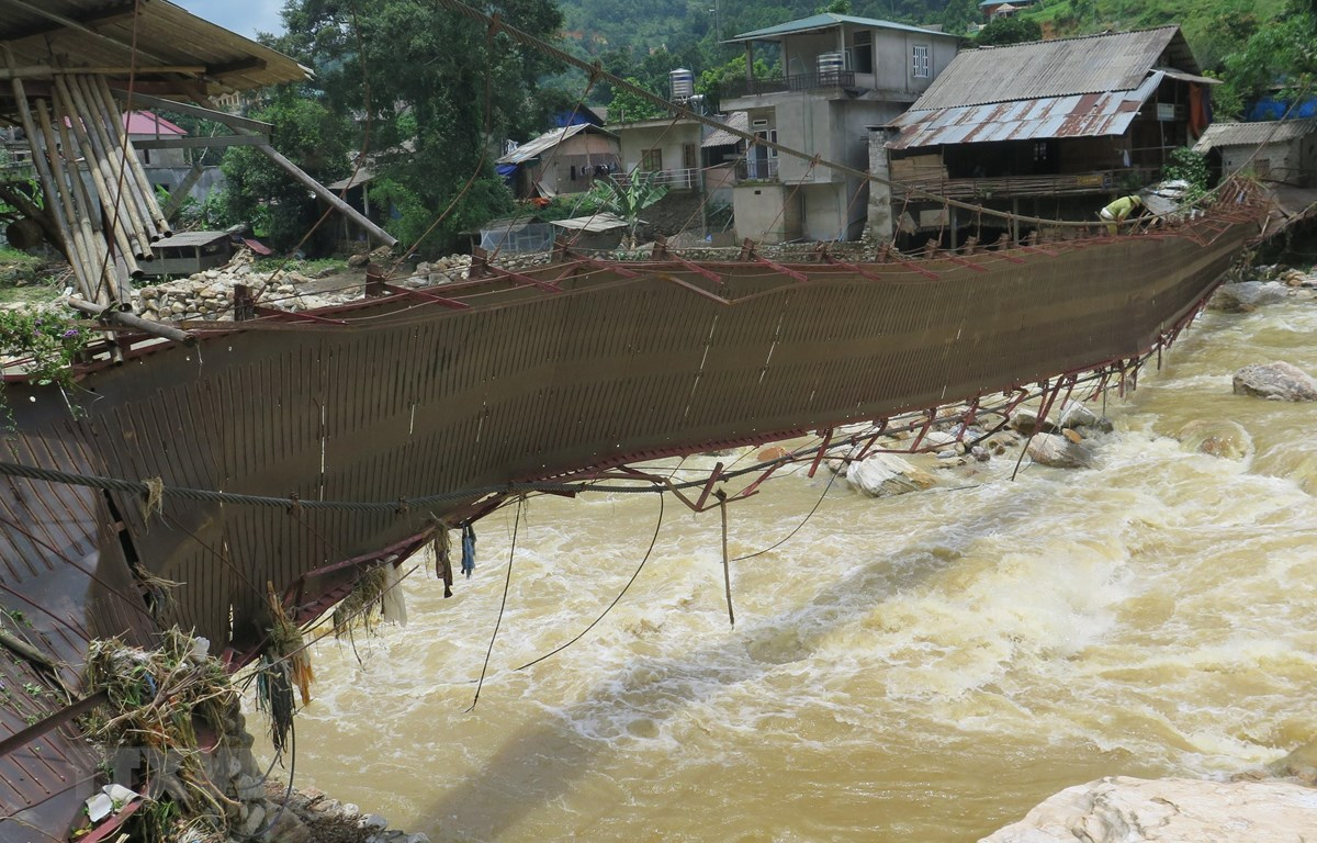 Một số người dân bất chấp nguy hiểm vẫn cố gắng đi qua cây cầu Bản Dền, xã Bản Hồ, huyện Sa Pa đã bị hư hỏng nặng sau trận lũ lớn. (Ảnh: Hương Thu/TTXVN)