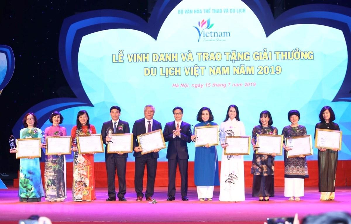 Phó thủ tướng Chính phủ Vũ Đức Đam trao giải cho các cơ sở đào tạo nguồn nhân lực, đơn vị truyền thông cho ngành du lịch. (Ảnh: Minh Quyết/TTXVN)