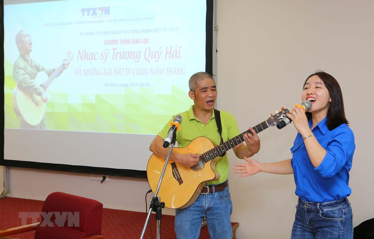 Nhạc sỹ Trương Quý Hải giao lưu hát cùng đoàn viên Thanh niên TTXVN. (Ảnh: Thành Đạt/TTXVN)