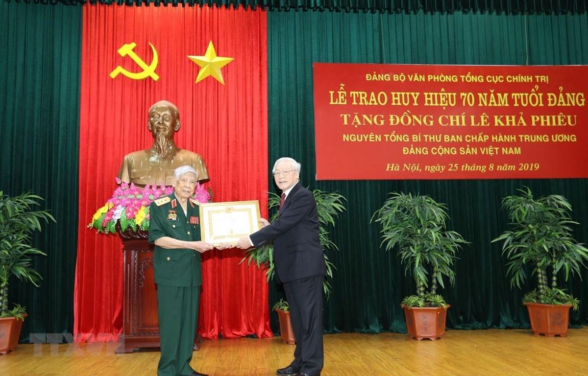 Tổng Bí thư, Chủ tịch nước Nguyễn Phú Trọng, Bí thư Quân ủy Trung ương trao Huy hiệu 70 năm tuổi Đảng tặng nguyên Tổng Bí thư Lê Khả Phiêu. (Ảnh: Trí Dũng/TTXVN)
