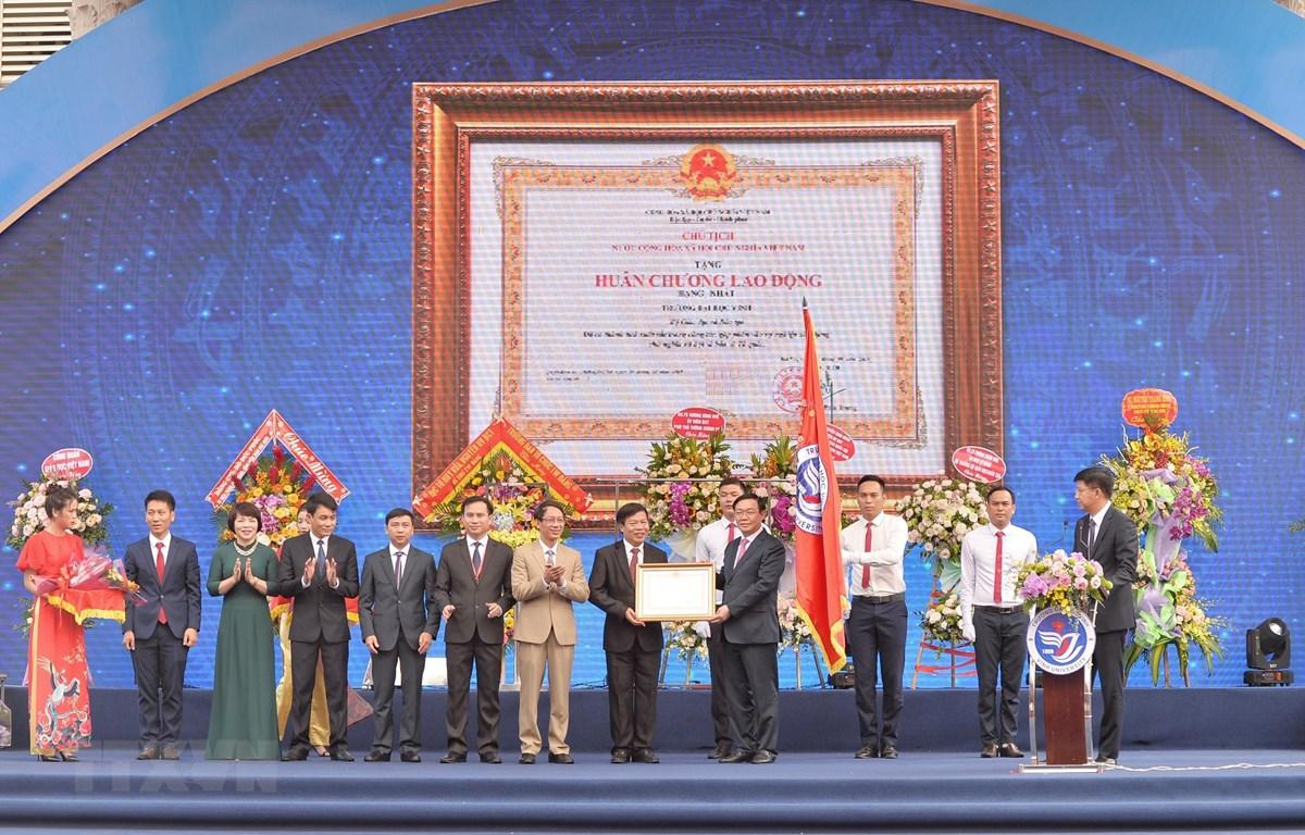 Phó Thủ tướng Vương Đình Huệ trao Huân chương Lao động hạng Nhất (lần thứ 2) cho trường Đại học Vinh. (Ảnh: Bích Huệ/TTXVN)