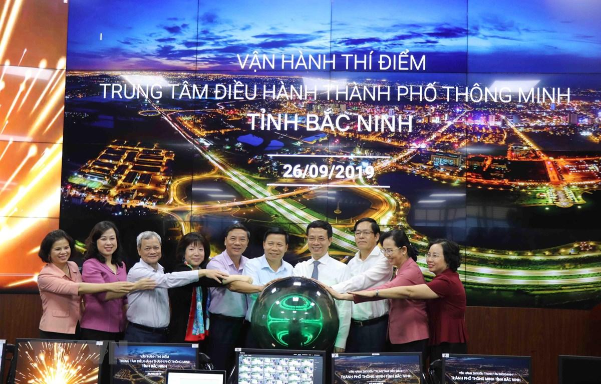 Bộ trưởng Bộ Thông tin và Truyền thông Nguyễn Mạnh Hùng (thứ 4 từ phải) và các đại biểu nhấn nút vận hành thử nghiệm chương trình. (Ảnh: Thanh Thương/TTXVN)