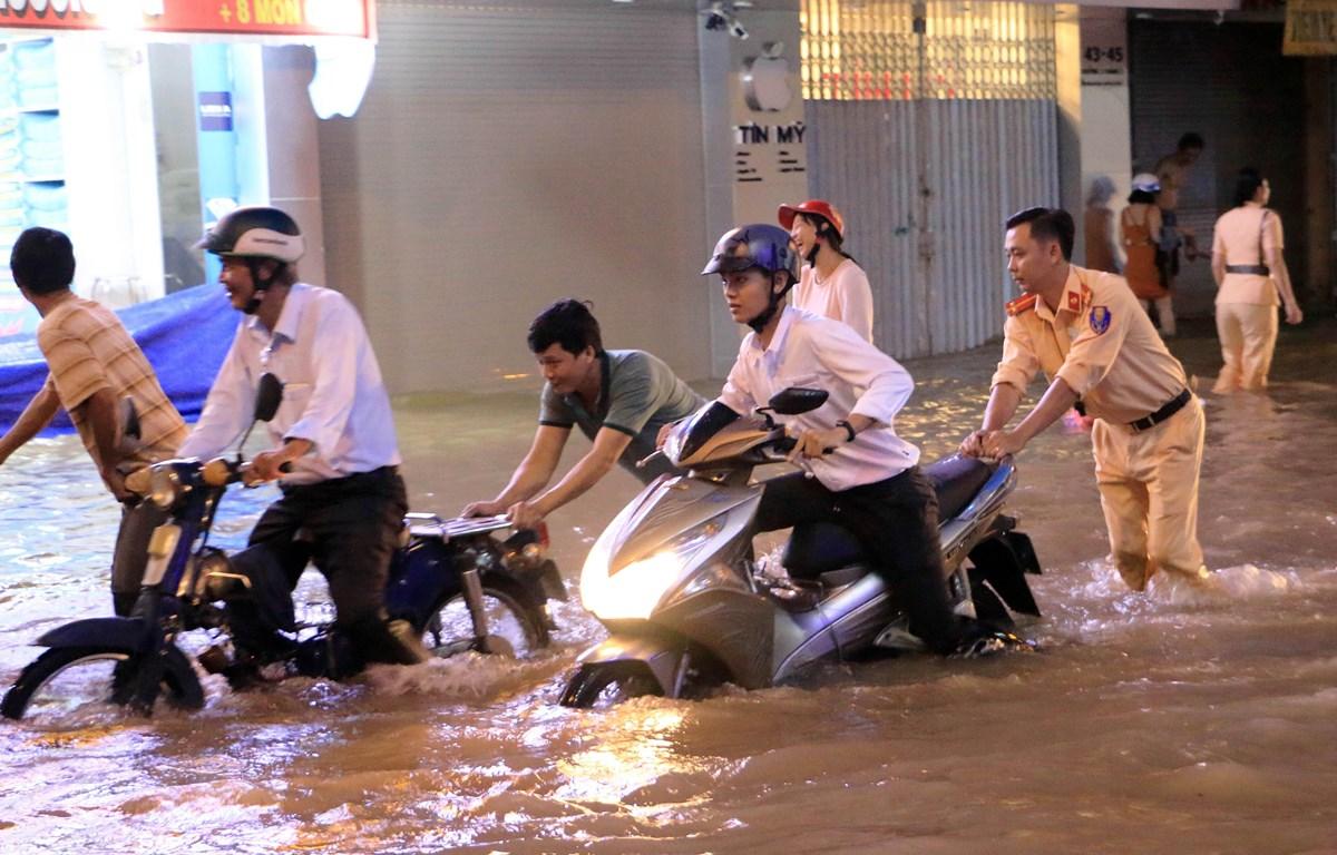 Lực lượng Công an giúp người điều khiển phương tiện giao thông di chuyển khỏi chỗ ngập tại đường 3 tháng 2, phường 1, thành phố Vĩnh Long. (Ảnh: Phạm Minh Tuấn/TTXVN)