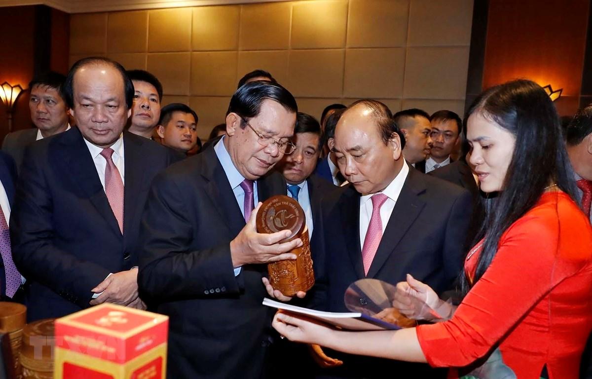 Thủ tướng Nguyễn Xuân Phúc và Thủ tướng Vương quốc Campuchia Samdech Techo Hun Sen xem các sản phẩm của doanh nghiệp trưng bày tại hội nghị. (Ảnh: Thống Nhất/TTXVN)